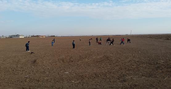 Çocuklar boş bırakılan tarlada futbol oynuyor